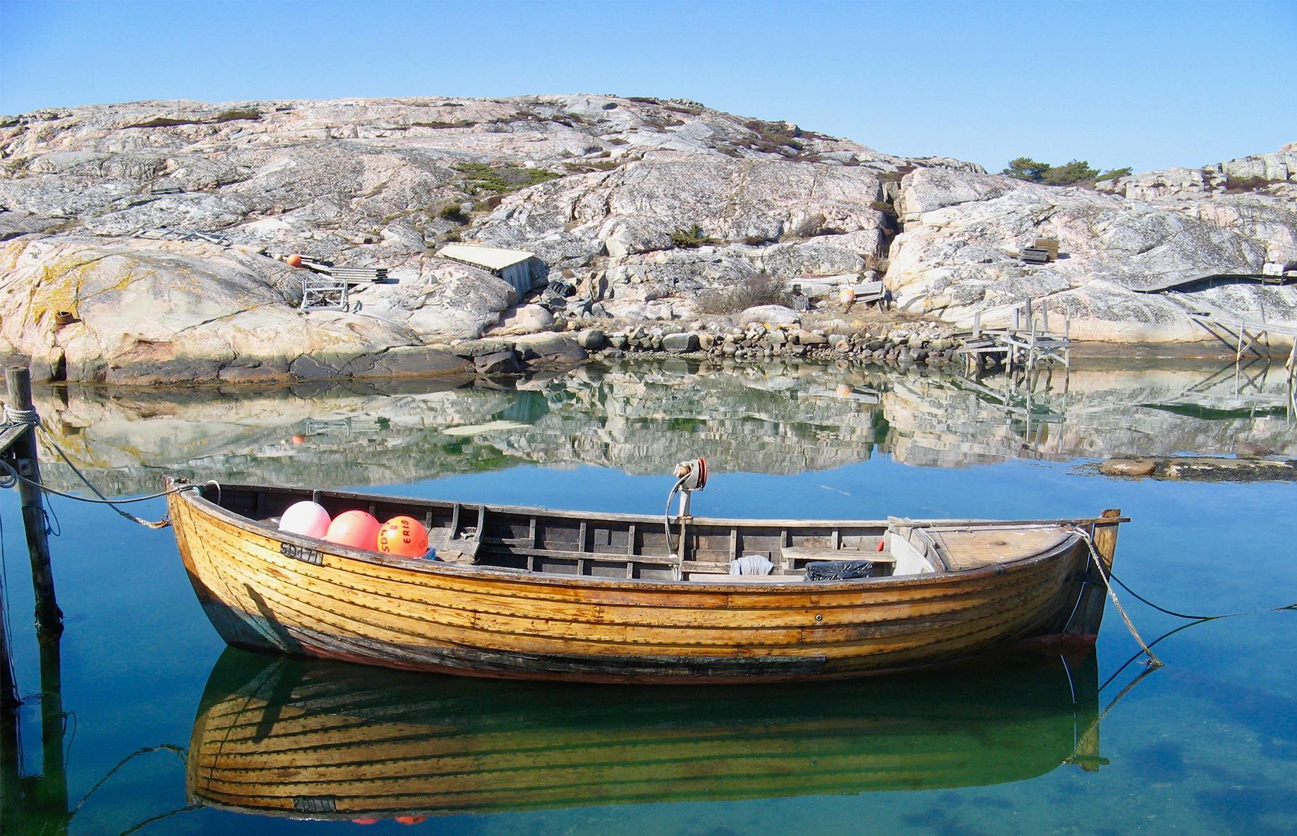 En gammal träbåt ligger tryggt i hamn vid havet